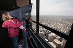 A girl looks through a telescop on the Willis Tower Skydeck, Chicago, IL