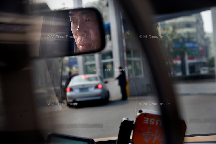 Chen Changyou, 47, is a taxi driver who came to Nanjing, Jiangsu, China, 28 years earlier.  One of the rare migrant workers who has received an urban resident permit, Chen Changyou earns about 4000RMB (about USD$500) a month and owns two homes.
