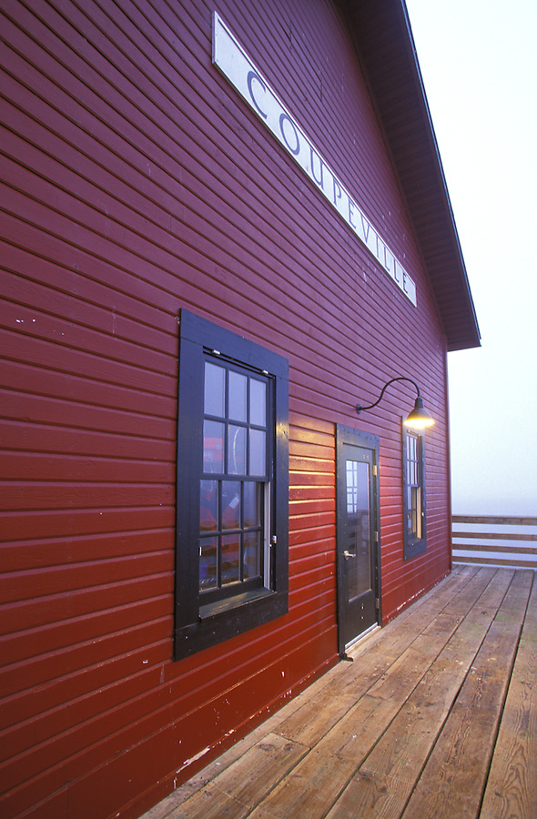 Red building, light, windows, and doorway on Coupeville Wharf early morning, Coupeville, Whidbey Island, Washington