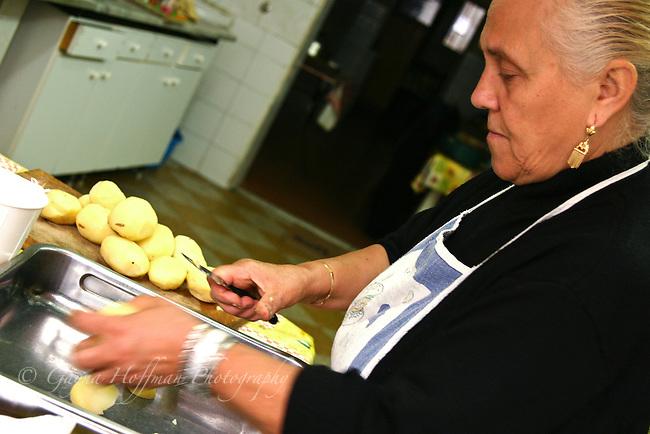 Sicilian woman peeling potatoes. Palermo, Italy