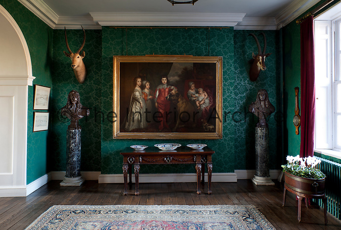A portrait of a young Charles II and his siblings, after Van Dyke hangs in the vibrant green entrance hall