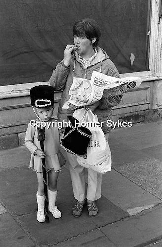 Preteen young girl in Drum Majorettes costume with her mother who is eating a take away fish and chip meal out of a newspaper. Newcastle upon Tyne, Tyne and Wear, England 1973