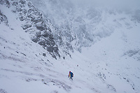 Hikers descends from mountain pass in winter storm, Moskenesøy, Lofoten Islands, Norway