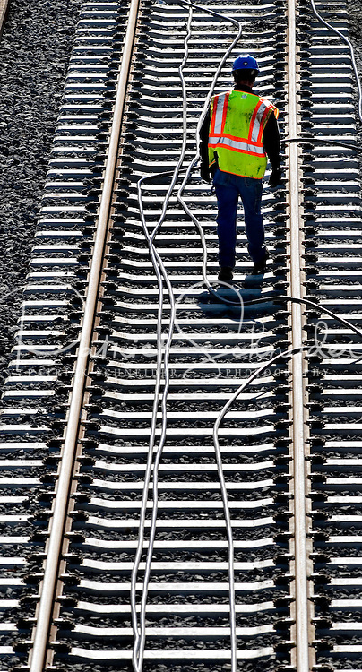 "02/26/07:  A construction worker threads wires during construction of Charlotte, NC's, new LYNX light rail lines, which opened on November 24th, 2007. More than 800 workers helped build the 9.6 mile LYNX Blue Line. The LYNX Blue Line offers fast, quiet, convenient light-rail service to 15 stations between uptown Charlotte and I-485 at South Blvd. Dozens of bus routes are timed to connect with trains at the Blue Line stations, making it easy to get to work, to shopping or wherever you need to be...NOTES FROM WIKIPEDIA: On November 24th, 2007, the first light rail line?a 9.6-mile (15.5-km) line known as the Lynx Blue Line? opened. It runs between Uptown Charlotte and stop short of Pineville, using a railroad right-of-way paralleling South Boulevard in its entirety. The line has 15 stations, it shares trackage with the Charlotte Trolley from the Atherton Mill station to the 7th Street station...Subsequently expected to open is a light rail line to the northeast. It will open in phases, with the first phase to reach 36th Street in 2013 and the second phase to reach I-485, at the University of North Carolina at Charlotte, in 2018. The corridor will be 14 miles (22.4 km) long, with 14 stations...On February 22, 2006, the Charlotte Area Transit System announced that its rapid rail lines will be called the ""Lynx."" (Lynx system map). The name fits in with the city?s cat theme (NFL team is Carolina Panthers; NBA team is Charlotte Bobcats, as well ""Lynx"" was mainly chosen because the light rail is about ""connectivity.""..The rapid rail cars will be black, silver and blue. Gold will appear around the ""Lynx"" logo to tie in the history of the Charlotte region being home to the first major U.S. Gold Rush...A commuter rail line is also planned. It will go from Uptown to the northern suburbs of Huntersville, Cornelius, Davidson, and Mooresville...Modern streetcars are also planned, with a circulator route around uptown as well as routes radiating out of downtown..... February 26, 200"