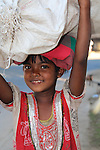 A young girl carrying goods on her head with a  smile