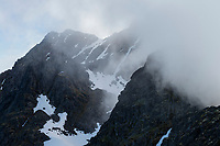 Steep north face of Himmeltindan mountain peak hidden in clouds, Vestvågøy, Lofoten Islands, Norway
