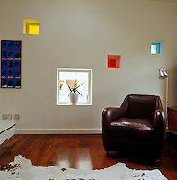 A leather armchair in the corner of the living room in which light pours through coloured glass squares in the wall