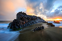 At sunrise, a long stretch of volcanic rock looks like a freight train standing in the water at Lumaha'i Tourists Beach (or Tourist Lumaha'i Beach), Kaua'i.