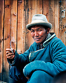 MONGOLIA, Khuvsgul National Park, a horseman Bayambasuren smokes a cigarette by Khuvsgul Lake, Toilogt Ger Camp