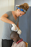 Nicky Hess, a Mennonite volunteer from the United States,  cleans the head injury of a boy in the clinic of the Loreto School in Rumbek, South Sudan. The school is run by the Institute for the Blessed Virgin Mary--the Loreto Sisters--of Ireland. Hess is an emergency room nurse from Lancaster, Pennsylvania.