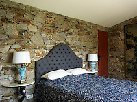 A stone wall in the master bedroom adds colour and texture