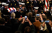 People take photos as the casket bearing the remains of former US President George H.W. Bush arrives at the US Capitol during the State Funeral in Washington, DC, December 3, 2018. - The body of the late former President George H.W. Bush travelled from Houston to Washington, where he will lie in state at the US Capitol through Wednesday morning. Bush, who died on November 30, will return to Houston for his funeral on Thursday. (Photo by Brendan SMIALOWSKI / AFP)