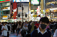 A young Japanese man in a black face mask in Hachiko Square, Shibuya, Tokyo, Japan. Thursday June 13th 2019
