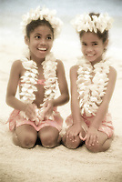 Two young girls with plumeria leis on the beach