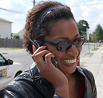 Newsday Reporter Nedra Rhone taking a phone call while covering a story on reaction to today's announcement of criminal charges  against three students accused of sexual molesting underclassmen at Mepham high School in Bellmore on Thursday October 2, 2003. (Newsday photo / Jim Peppler).