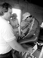 Dale Earnhardt is surrounded by reporters as he sits on the back of his race car at Daytona International Speedway in July 1987.(Photo by Brian Cleary)