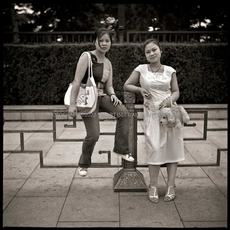 6/26/2005--Beijing, China..Fang Yan Mei, 17 (left) and Yu Wenhui, 20 (right), both from Hunan Provine, wait outside Mao's Mausoleum on Tiananmen Square. ..Photograph By Stuart Isett.All photographs ©2005 Stuart Isett.All rights reserved.