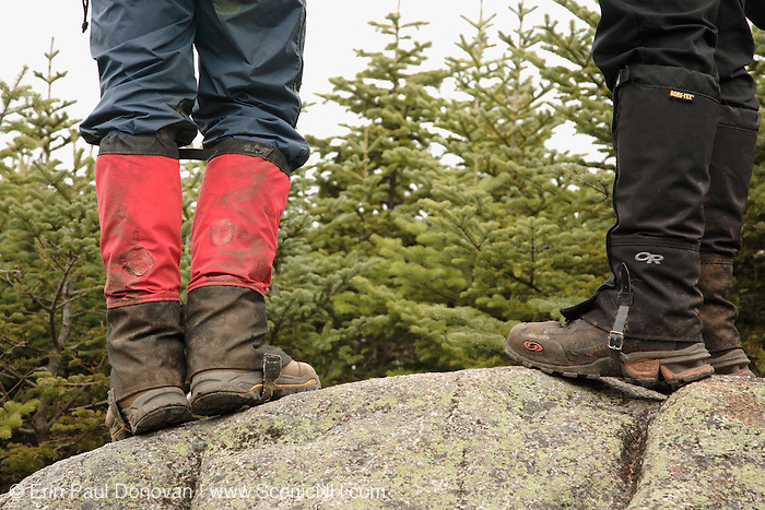 A hiking wearing gaitors on a hiking trail in the White Mountains, New Hampshire USA