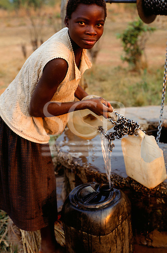 Kapatu, Zambia. Woman filling her water containter at the village well.