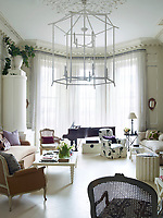In the sitting room, a giant 'Giacomettiesque' chandelier made of metal pipes and tape dominates the room. The eclectic style is offset by calm: white walls, white wood floors, relatively spare arrangements of traditional furniture and neutral upholstery.