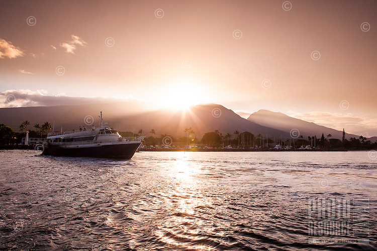 Tourists sail out of Lahaina Harbor for a sunset cruise off the coast of Maui.