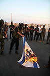 "Palestinian militants of the military wing of the popular resistance committees ""El-Nasser Salah El-Deen brigades"" burn the Israeli Flag during  a protest calling for lift the siege on Gaza, in Deer El-Balah town Central Gaza Strip."