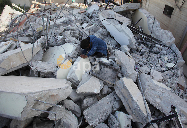 Palestinians inspect the rubble of of their house that were demolished by the Israeli bulldozers, in the village of Qabatiya south of Jenin, on April 4, 2016. The three Palestinians to whom the houses belonged were shot dead in Jerusalem at the beginning of February after killing an Israeli police officer and wounding another in an armed attack outside Damascus Gate in Jerusalem's Old City. Photo by Nedal Eshtayah