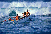 Three women paddling an outrigger canoe through the waves