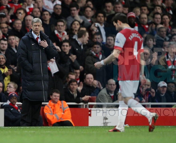 Arsenals Arsene Wenger watches as Cesc Fabregas goes off injured