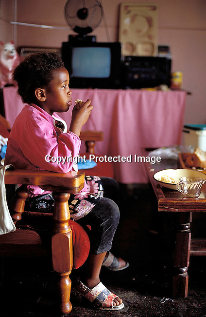 PPCHILD50398.People.  Children.  A young black girl eating food inside her home. TV dinner.©Per-Anders Pettersson / iAfrika Photos