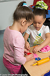 Education preschool 3-4 year olds art activity play dough two girls working together