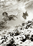 ARUBA, young woman looking at fish while swimming along sandy ocean floor