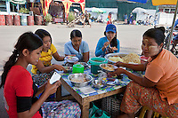 Myanmar, Burma, Yangon.  Customers Enjoy Lunch at a Street Food Vendor's Stand.  The owner is wearing thanaka paste on her face as a cosmetic sunscreen.