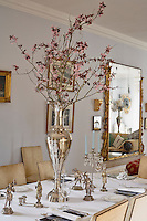 An arrangement of pink flowering branches in silver vase on dining table, Loughcrew House, County Meath, Ireland