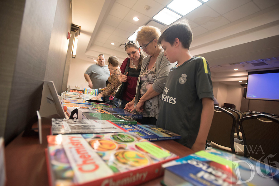 NWA Democrat-Gazette/J.T. WAMPLER  Chance Wiser,11, (from right), his grandmother Sally Wiser and mother Rachel Wiser, all of Rogers, look over textbooks Tuesday July 19, 2016 at a presentation by Arkansas Connections Academy. The virtual public school for students in K through 9th grades offers parents throughout Arkansas the opportunity to learn more about the virtual public school during local information sessions.<br /> During the session, participants will discuss the family&rsquo;s role in the education process through topics such as organizing the home for the most effective schooling environment and balancing time when more than one child is enrolled in the program. Participants also learn how Arkansas Connections Academy&rsquo;s community coordinators arrange field trips and extracurricular activities for students and parents across the state as a means of education, fun and networking with others enrolled in the school.