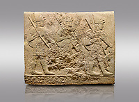 Picture &amp; image of Hittite sculpted orthostats of Long Wall Limestone, Karkamıs, (Kargamıs), Carchemish (Karkemish), 900-700 BC. Anatolian Civilisations Museum, Ankara, Turkey<br /> <br /> Soldiers. Figure of three helmeted warriors. They have their shield in their back and their spear in their hand. The prisoners in their front are depicted as small. The lower part of the orthostat is decorated with wring / braiding motifs.<br /> <br /> On a gray background.