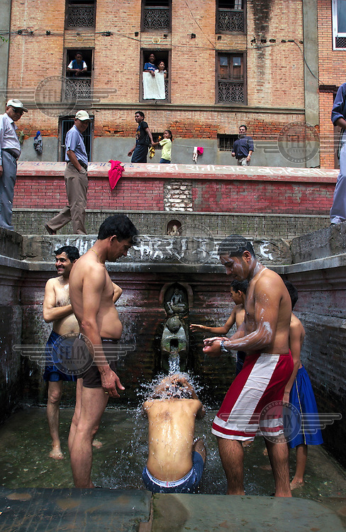 Washing in a public conduit outside the Kumbeshwar temple.
