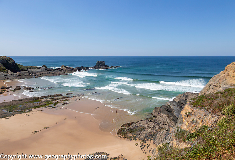 Sandy Carvalhal beach in bay between rocky headlands at Parque Natural do Sudoeste Alentejano e Costa Vicentina, Costa Vicentina natural park, near Brejão, south west Alentejo, Alentejo Littoral, Portugal, Southern Europe. One small figure of a person is visible standing on the shoreline.