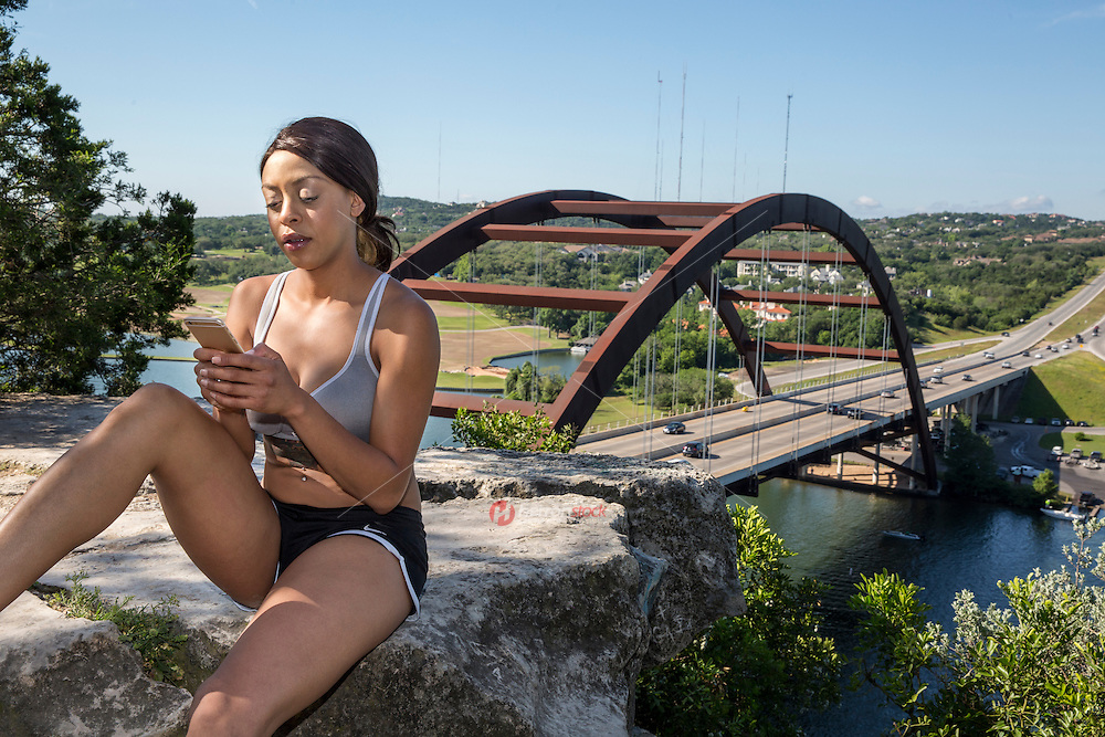 Beautiful African-American athlete woman texting on a mobile smartphone on a cliff overlooking the 360 Bridge on Lake Austin, Texas.