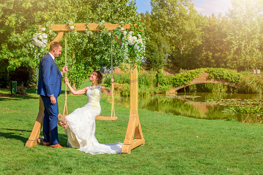 Bride on swing smiling at Groom