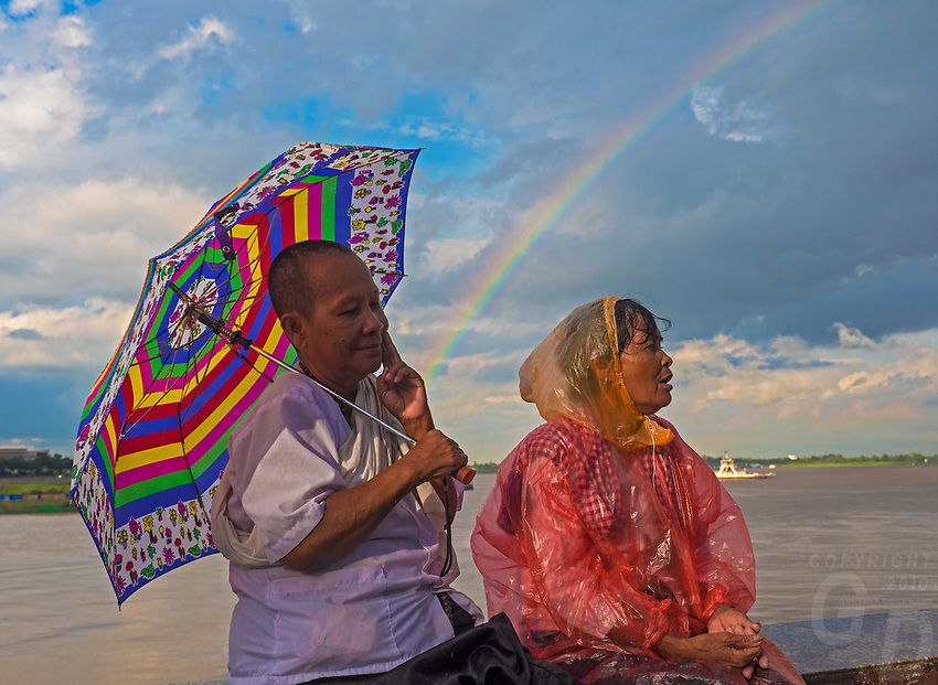 Women at the Phnom Penh River front during a rain shower with a Rainbow over the Mekong River, Cambodia.