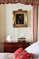 A traditional bedroom with a neutral striped pattern wallpaper and a four poster bed with red hangings. A gilt framed painting hangs on the wall above a chest of drawers.