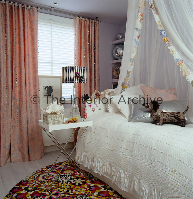 A girl's bedroom has a bed canopy decorated with a pretty border