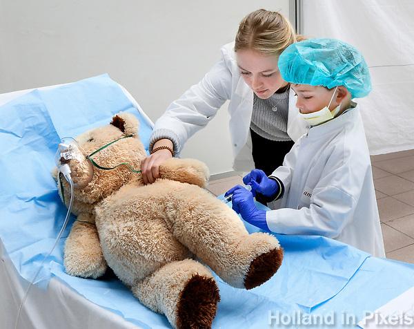 Nederland Amsterdam 2017 . Teddy Bear Hospital in het AMC ziekenhuis.  ( Foto mag niet in negatieve context gebruikt worden ). Teddy Bear Hospital (TBH) is één van de grootste projecten van IFMSA-NL. Het TBH is een rollenspel. Dat houdt in dat kleuters van vier t/m zes jaar hun beer of een andere knuffel meenemen naar een nagebootst ziekenhuis. Geneeskundestudenten spelen voor arts en behandelen de knuffels. Het doel van Teddy Bear Hospital is om kinderen op een speelse manier kennis te laten maken met de gezondheidszorg, om zo de angst voor dokters en het ziek-zijn enigszins weg te nemen. Bovendien leert het medische studenten om te gaan met kinderen en trainen ze hun communicatieve vaardigheden.  (  Met behulp  van Photoshop is een prop papier van de grond verwijderd ) . Foto Berlinda van Dam / Hollandse Hoogte