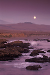 Evening moonrise over hills and rock coast at Piedras Blancas, near San Simeon, California
