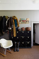An Eames rocking chair sits in front of coat hoots, heavy with textured coats and scarves.