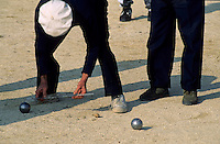 Man measuring the distance between two boules with a ruler to determine a winner, Provence, France.