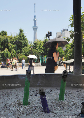 July 12th, 2011, Tokyo, Japan - The Tokyo Sky Tree, a terrestrial digital communication tower, looms in the summer sky in the background as sticks of incense burns in the hearth at Sensoji Buddhist Temple in downtown Tokyo, where the mid-afternoon temperature reached 32 degrees Celsius (89 degrees Fahrenheit) on Tuesday, July 12, 2011. The Japanese government warned the public not to cut back too much on the use of air conditioners in the midst of national drive to conserve energy, citing the possibility of heat stroke. Nearly 7,000 people were hospitalized for heat exhaustion in June, three times more than last year. Weather officials said June's heat wave sent the mercury rising in parts of Japan to their highest levels since 1961. Temperatures in downtown Tokyo reached 35 degrees Celsius (95 degrees Fahrenheit) on June 29 - the third highest in June since the Meteorological Agency began compiling comparable records in 1875. (Natsuki Sakai/AFLO)