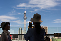 Japanese women tourists take a photo of Tokyo Skytree from the Tourist Center in Asakusa, Tokyo, Japan. Thursday June 28th 2018