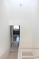 A elevated view from the top of a staircase looking down into a minimalist hallway.